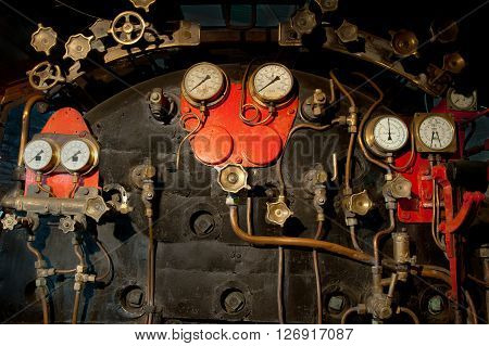 The intricate detail of a steam locomotive cockpit is on display.