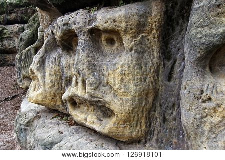 Scary Stone Heads - rock sculptures of giant heads carved into the sandstone cliff