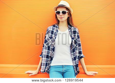 Fashion Woman Wearing A Straw Hat And Sunglasses Over Colorful Orange Background
