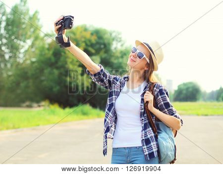 Young woman makes self-portrait on smartphone outdoors