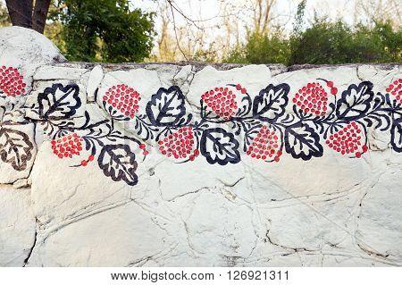 Petrykivka traditional ukrainian painting on the white stone fence. The fence on island Khortytsia in ukrainian city Zaporizhia.