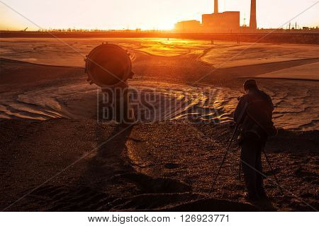unusual industrial landscape. photographer at sunrise on the industrial background.