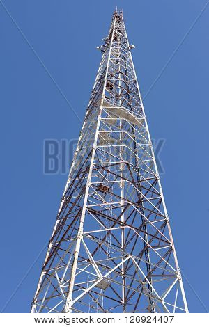 High communication tower against the blue sky