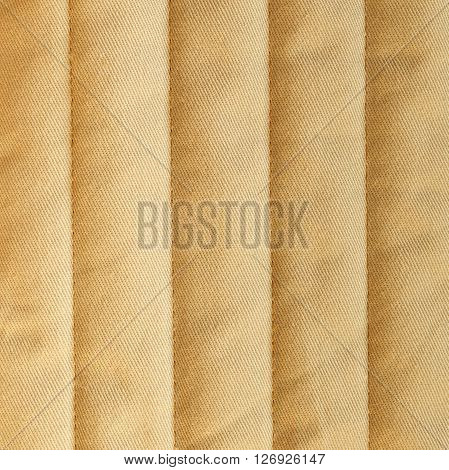 Brown quilted textiles with insulation. Vertical stripes. Close up fragment of the top view.