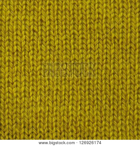 Yellow curry wool knitted fabric. Close up fragment of the top view.