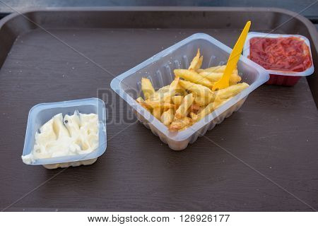 French fries with ketchup and mayonnaise on a brown tray