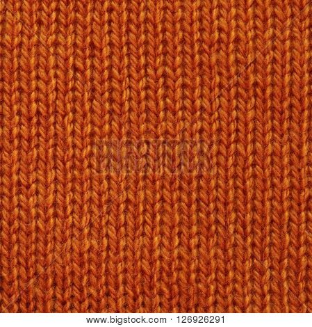 Moderately orange wool knitted fabric texture. Close up fragment of the top view.
