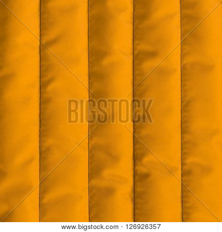 Orange quilted textiles with insulation texture. Vertical stripes. Close up fragment of the top view.