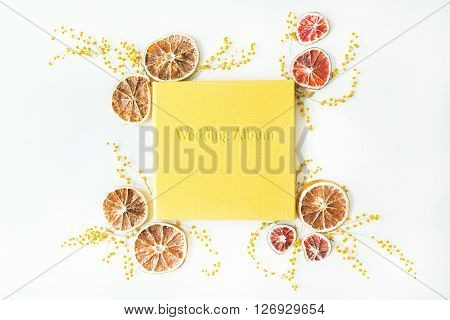yellow wedding photo album and frame with dry oranges and branches of mimosa isolated on white background. flat lay overhead view