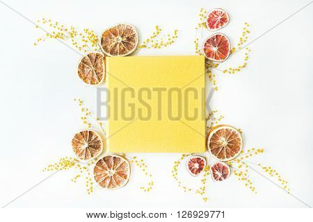 yellow wedding or family photo album and frame with dry oranges and branches of mimosa isolated on white background. flat lay overhead view