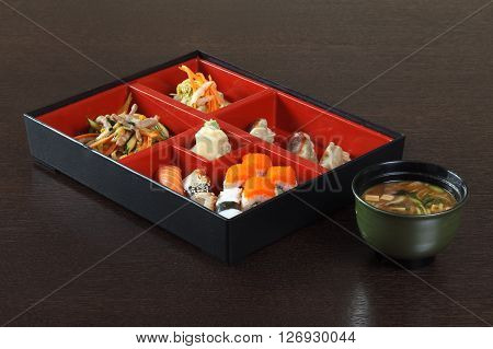 Japanese cafe lunch of sushi miso soup gyoza tuna ginger red caviar wasabi the pieces of meat sashimi and salad. Container with compartments for dishes on a wooden table.