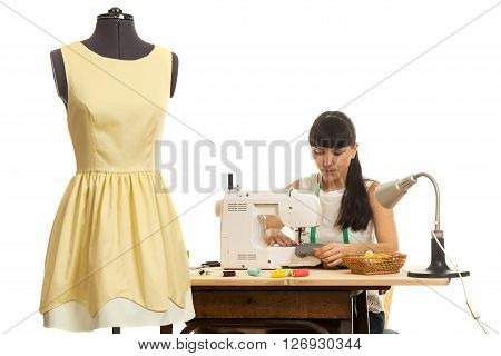 the seamstress sews a product on a table on the sewing machine