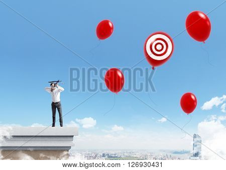 Businessman aiming at balloons with target standing on pedestal in the sky