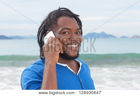 Funny african american guy with dreadlocks at phone outdoor at beach with ocean in the background