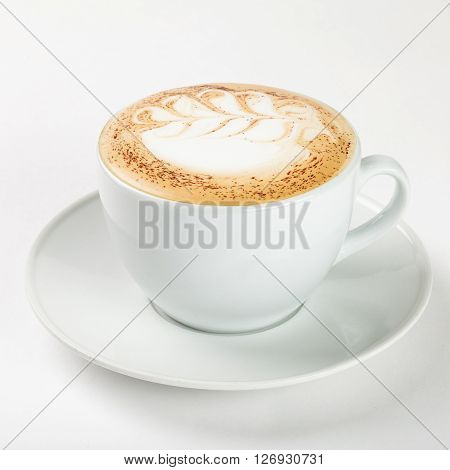 Delicious cappuccino in a white cup on the plate on white background. Close up side view.