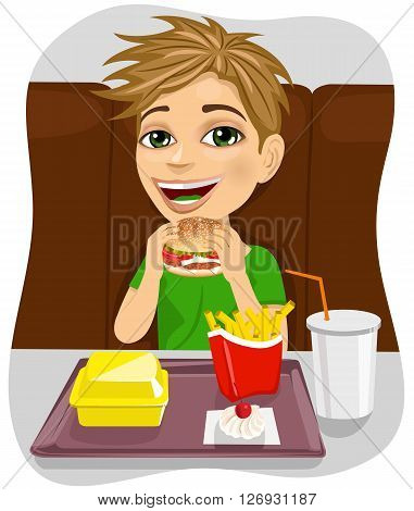 young boy eating cheeseburger with french fries in fast food restaurant