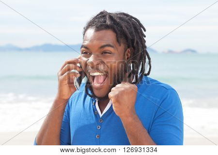 Exciting african american guy with dreadlocks at phone outdoor at beach with ocean in the background