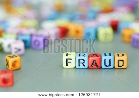 Close up of Fraud word on colorful dices