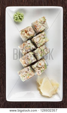 Sushi rolls on a plate with tuna and ginger on dark brown wooden table. Top view.