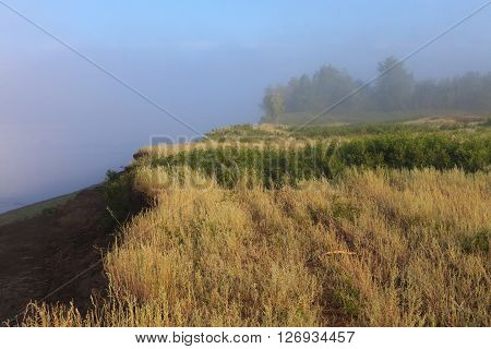 Mysterious Volga riverside in fog. Misty dawn early morning nature grassland landscape view in Russian countryside. ** Note: Visible grain at 100%, best at smaller sizes