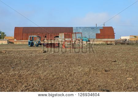 Abandoned farm equipment field barn. The landscape of the Russian village on the Volga river ** Note: Visible grain at 100%, best at smaller sizes