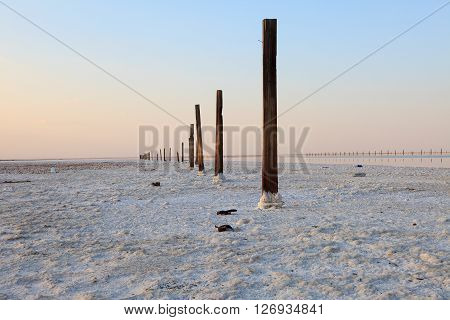Wooden pillars and a salt crust on the surface of the desert and the lonely mountain. Evening landscape. The extraction of salt.