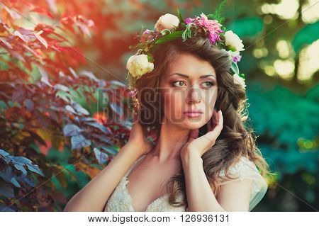 Portrait of pretty bride brunette posing in white wedding dress with hairstyle and bright makeup. Wedding hairstyle and bride's make-up