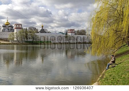 MOSCOW RUSSIA - APRIL 21 2016: Lone fisherman on the pond at the Novodevichy Monastery Moscow. Mid-April.