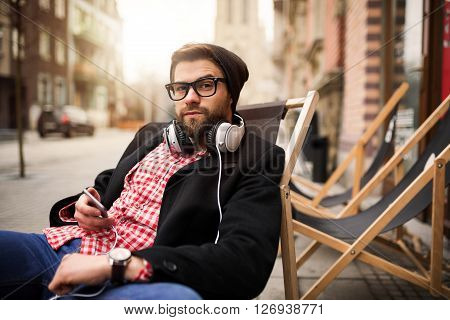 Man Relaxing In Front Of Cafe