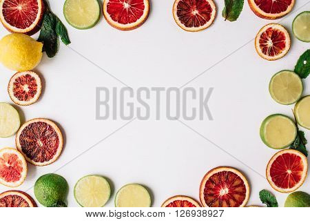 Red oranges yellow lemons green limes and mint pattern isolated on white. Flat lay. Wraith frame