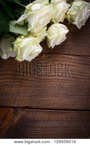 Bouquet of white rose flowers on wooden table. Copy space