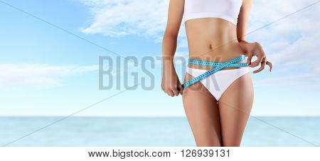 woman holding blue meter with hands near waistline isolated on summer sky and sea background