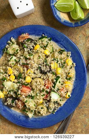 Quinoa salad with sweet corn olive tomato cucumber and chives on plate photographed overhead on slate with natural light
