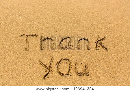 Thank you - inscription by hand on golden beach sand.