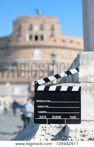 Movie clapper board with Rome landmark castle out of focus in background