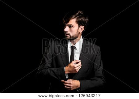 Stylish young businessman on black background. Businessman looking aside and correcting cuffs