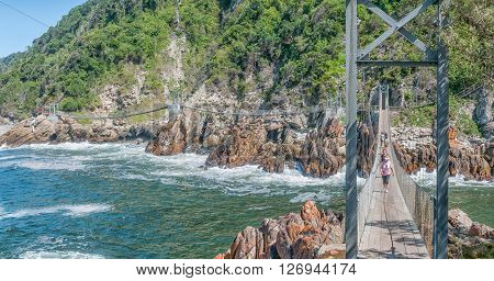 STORMS RIVER MOUTH SOUTH AFRICA - FEBRUARY 29 2016: Unidentified tourists on the suspension bridge over the mouth of the Storms River
