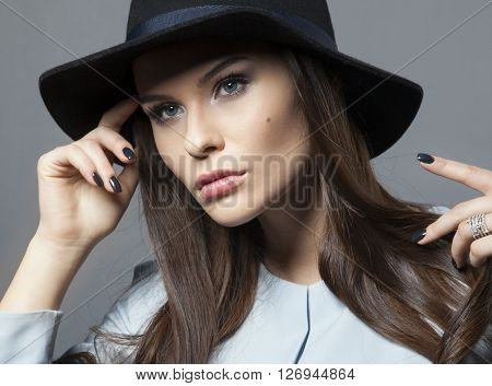 Beautiful model in a hat with beautiful makeup and blue dress studio photoshoot