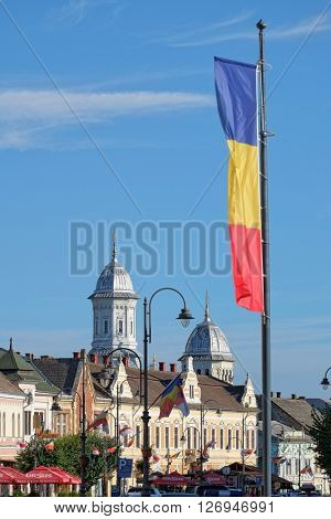 TURDA, ROMANIA - AUGUST 09, 2015: the Romanian flag waving on skyline of downtown Turda in Transylvania