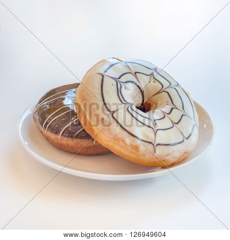 White Chocolate And Chocolate Donuts On Plate