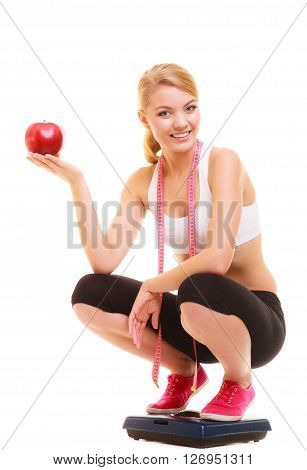 Happy joyful young woman girl with measuring tape on weighing scale holding apple. Slimming and dieting. Healthy lifestyle nutrition concept. Isolated on white background.