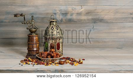 Golden lantern and vintage mill. Raisins and dates fruits on wooden background. Oriental arabic decoration