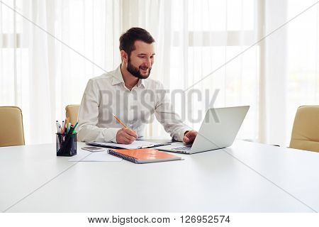Beard smiling man working on his laptop and writing some data in a pad  in the white office