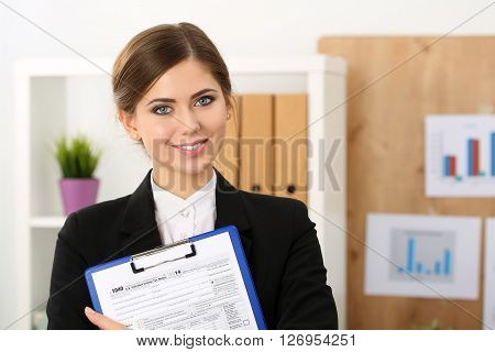 Beautiful Female Accountant Hold Income Tax Return Form