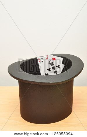 A magicians hat with cards in the inside