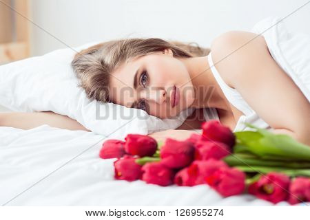 Just woke up.  Pleasant charming woman lying in bed with flowers and looking at you while feeling delighted