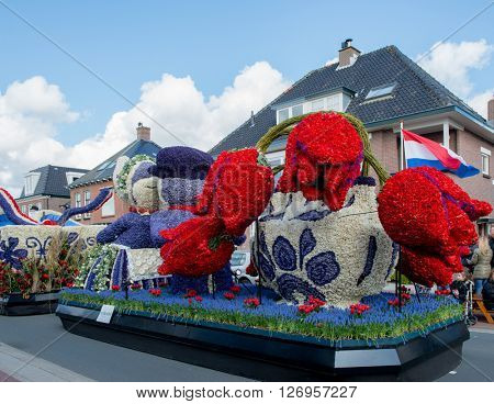 HILLEGOM, THE NETHERLANDS - APRIL 23, 2016: Moving platform in a form of a traditional Dutch kissing couple and vase with tulips. Decorated with flowers. Traditional flowers parade