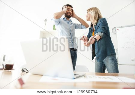 I do not want even to hear. Beautiful young woman is explaining her ideas to her colleague. She is pointing finger at laptop and smiling. Man is closing his ears with disagreement