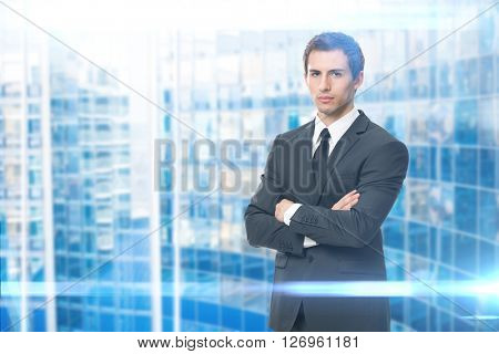 Portrait of serious businessman with crossed hands, blue background. Concept of leadership and success