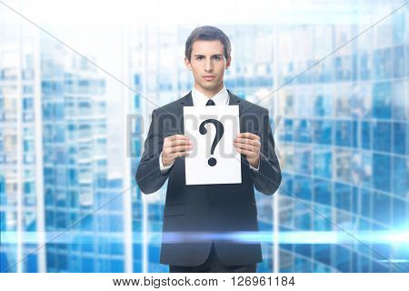 Portrait of business man handing question mark, blue background. Concept of problem and solution